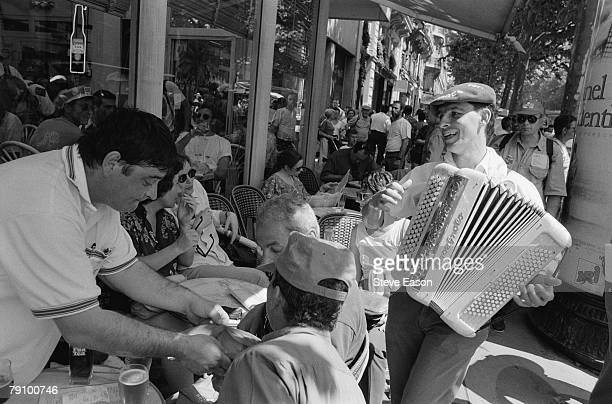 An accordionist plays outside a Parisian cafe during a demonstration by French union federations against the planned privatisation of the French...