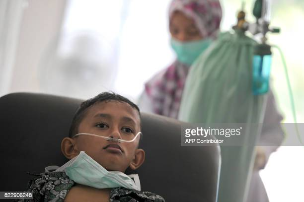 An Acehnese boy undergoes treatment for lung infection from thick smoke due to peat forest fires in Meulaboh Aceh province on July 26 2017...