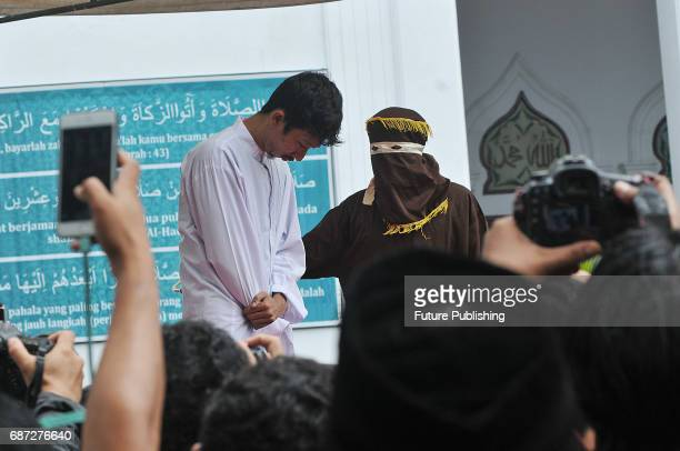 An Acehnese man is being whipped in public for violating sharia law on May 23 2017 in Banda Aceh Indonesia About four Acehnese couple received 25 up...