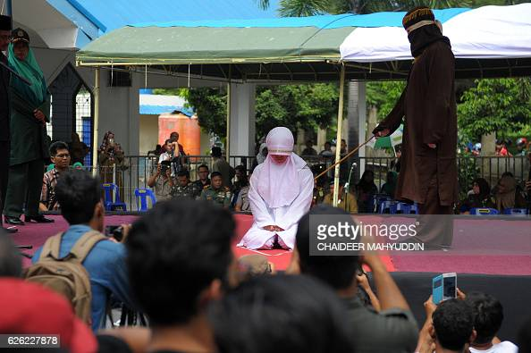 An Acehnese religious officer canes a woman 100 times for having sex outside marriage which is against sharia law in Banda Aceh on November 28 2016...