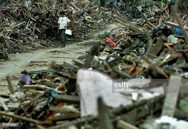 An Acehnese tsunami surviving young man walks along debris of houses in Banda Aceh 29 January 2005 Peace negotiators for the Indonesian government...