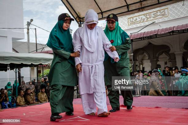 An acehnese woman escorted by the sharia police women who will receive lashes of cane in public from an executor known as 'algojo' for spending time...