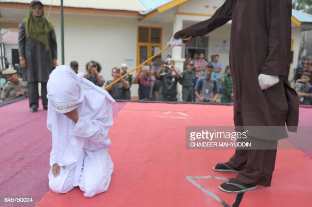TOPSHOT An Acehnese woman gets caned by a religious officer for spending time in close proximity with a man who is not her husband which is against...