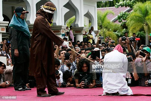 An Acehnese woman is escorted by members of the Sharia police on a stage before her punishment whipped for 'immoral acts' with a cane as punishment...