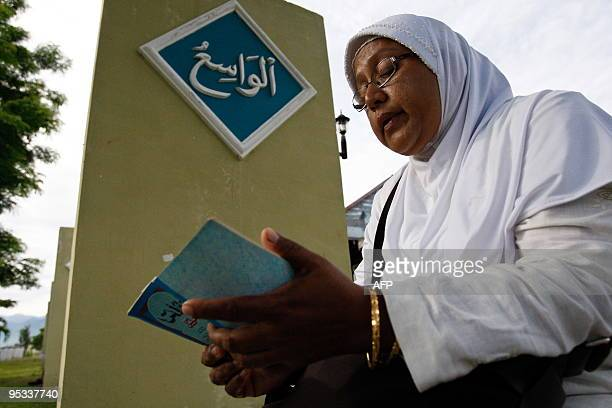 An Acehnese woman read a copy of the Koran for their beloved ones who died in the earthquake and the tsunami at Ulee Lheu mass grave in Banda Aceh on...