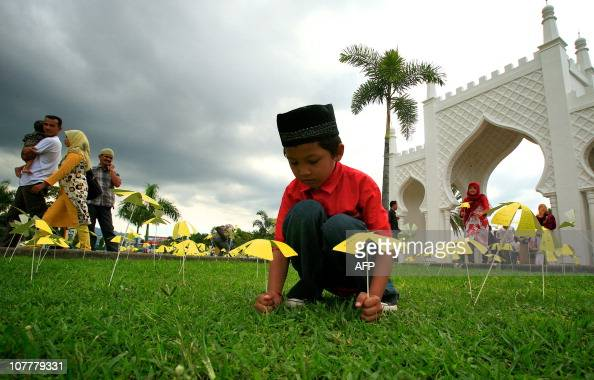 An Acehnese young boy puts paper flowers into the ground provided by Japanese people from Kobe as part of the 6th earthquake and tsunami anniversary...