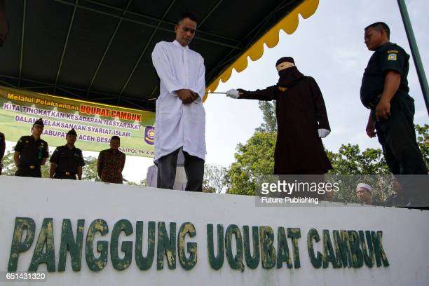 An Acehnesee man is whipped in public by Sharia police for violating the Sharia law on March 10 2017 in Banda Aceh Indonesia The man was sentenced to...