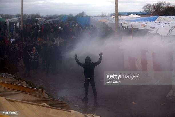 An acivist is sprayed with a water cannon as part of the 'jungle' migrant camp is cleared on February 29 2016 in Calais France The French authorities...