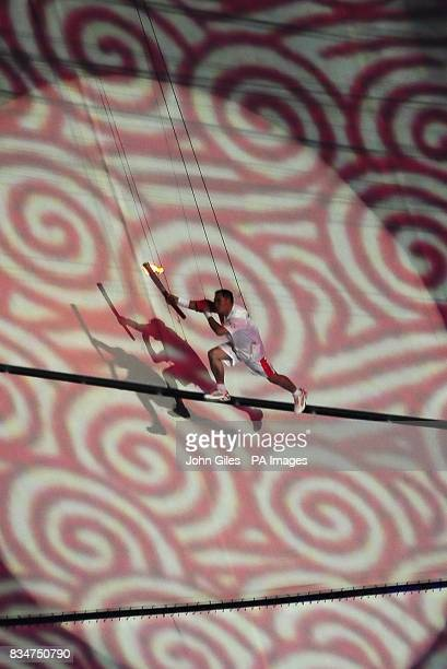 An acrobat carries the Olympic torch during last leg of the torch relay during the Beijing Olympic Games 2008 Opening Ceremony at the National...