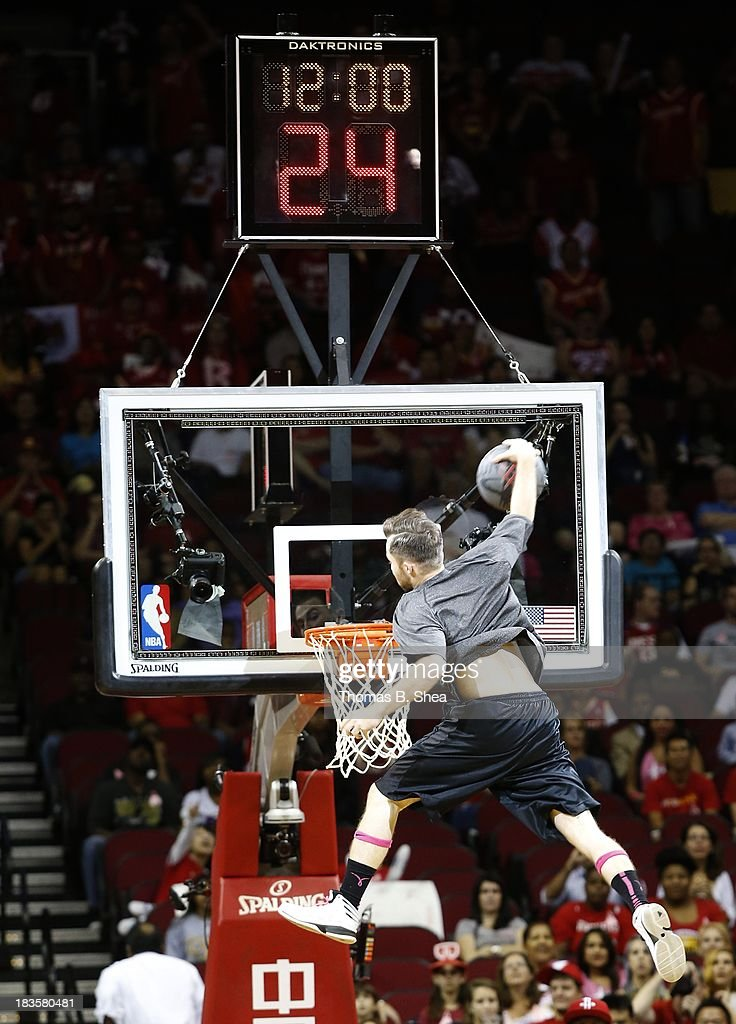 An acrobat dunks the ball during a timeout in the game of the Houston Rockets against the New Orleans Pelicans in a preseason NBA game on October 5, 2013 at Toyota Center in Houston, Texas. The Pelicans won 116 to 115.