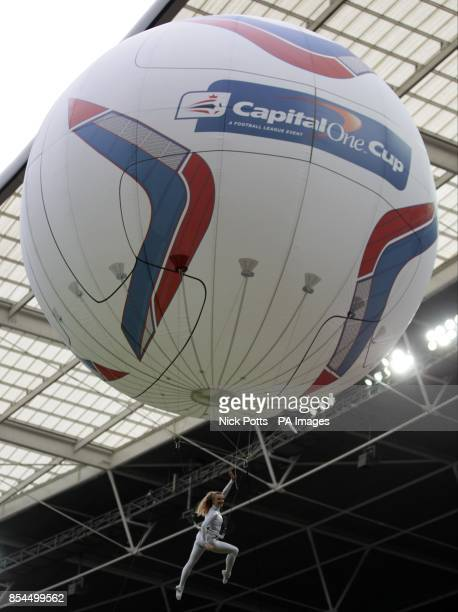 An acrobat hangs below a giant inflatable Capital One Cup football