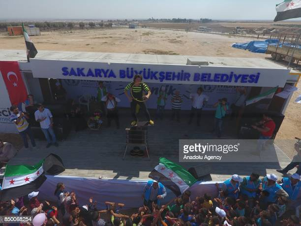 An acrobat performs as Syrian kids look on during 'Azaz 2017 Festival' organised by International Refugee Rights Association at The University of...