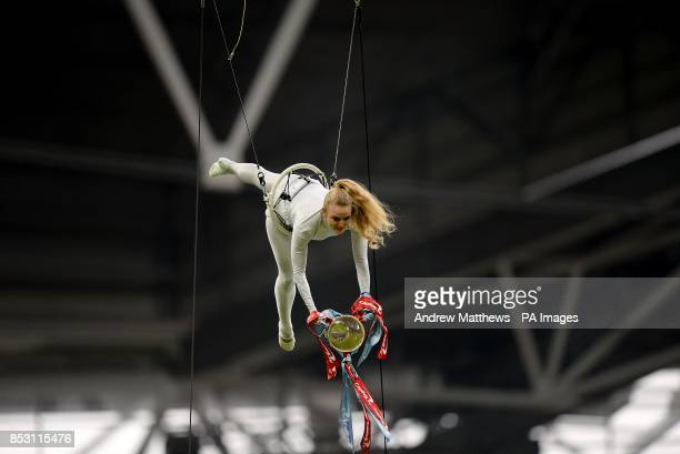An acrobat performs with the Capital One Cup above the pitch before kickoff