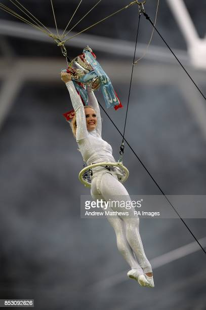 An acrobat performs with the Capital One Cup before kickoff