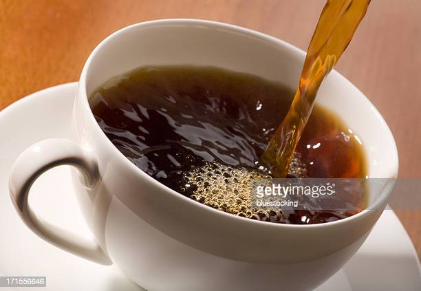 An action shot of black coffee being poured into a cup