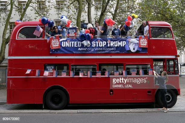 An activist adjusts US flag bunting attached to a 'Stop Trump' battle bus in London on September 21 2016 in a campaign run by campaign group Avaaz to...