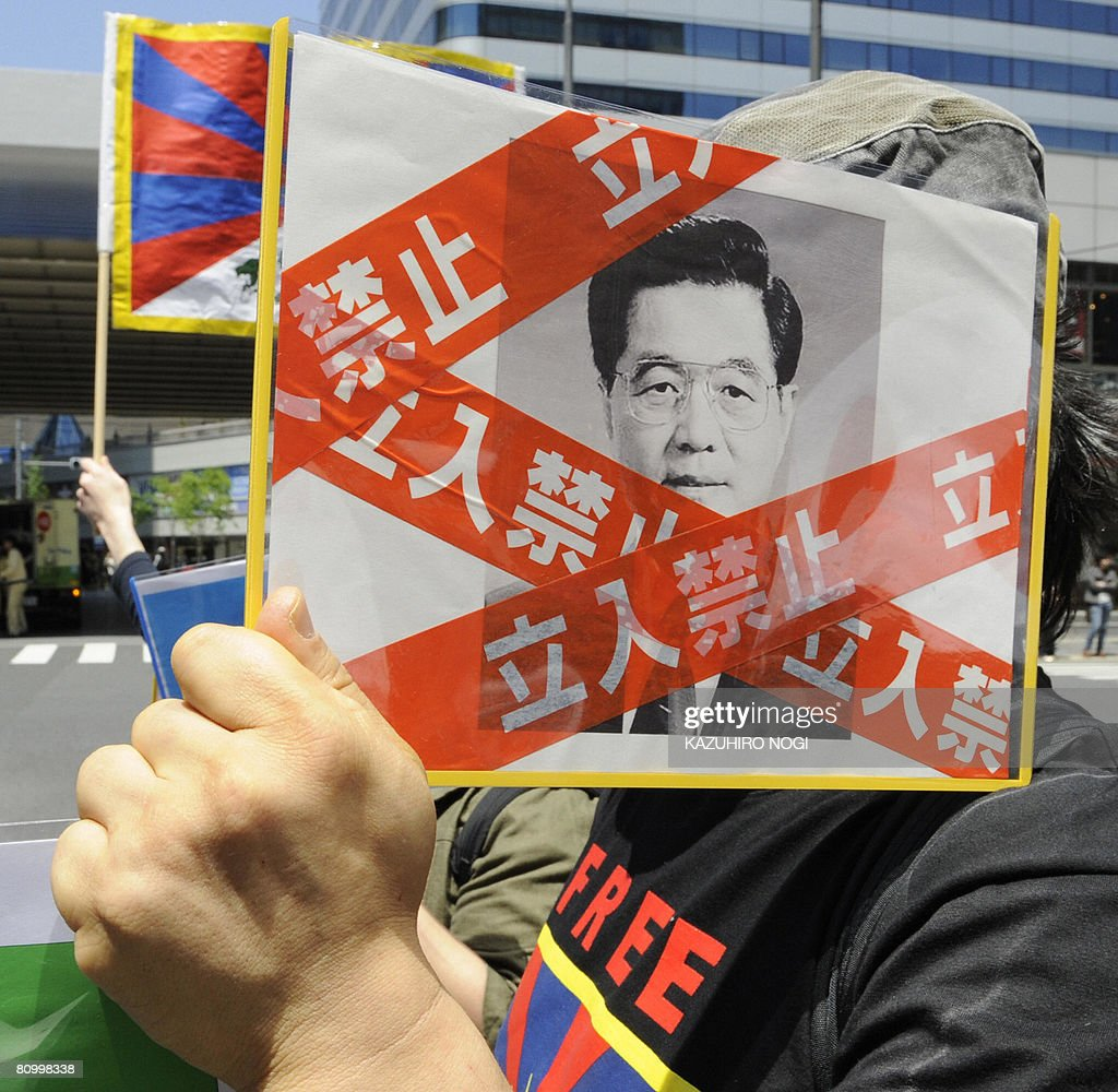 An activist against China holds a picture of Chinese President Hu Jintao with a taping of 'Keep Out' during a demonstration march against the visit of the Chinese leader in downtown Tokyo on May 6, 2008. President Hu Jintao was due in Japan on the first visit here by a Chinese head of state in a decade as Asia's two largest economies try to patch up after decades of friction. AFP PHOTO/Kazuhiro NOGI