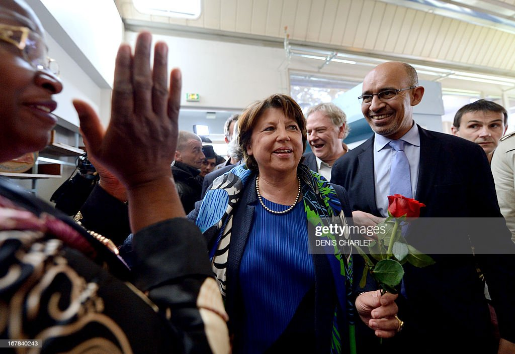 An activist applauds as French Socialist Party (PS) national Secretary Harlem Desir (R) and Lille's Mayor and former minister Martine Aubry (C) arrive to attend a socialist meeting and lunch, the 'Fete de la rose' in Tourcoing, northern France, on May, 1, 2013, as part of the May Day events.