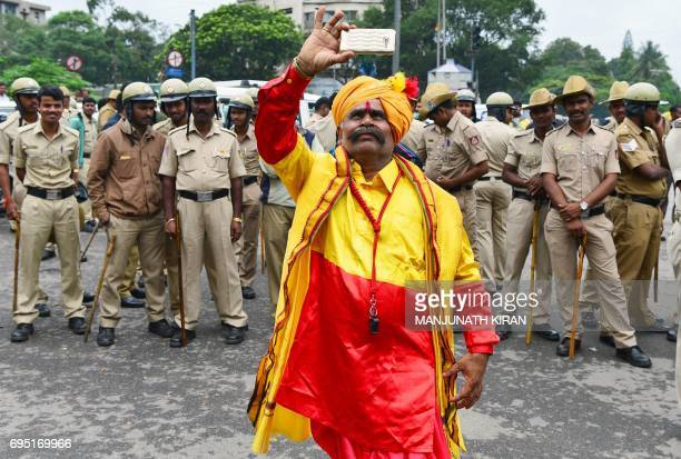 An activist attired in the colours of the Karnataka state flag takes photographs on his mobile phone in front of policemen during a protest in...