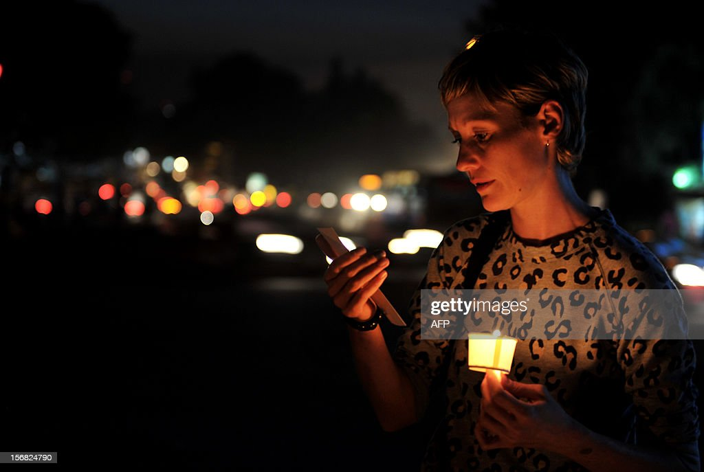 An activist belonging to the Coalition for Sexual Minority Rights (CSMR) reads a pamphlet while taking part in a candle light vigil held as part of Transgender Day Remembrance held in Bangalore on November 22, 2012. The candle light vigil marks the start of the annual 10-day Bengaluru Pride and Karnataka Queer Habba 2012. AFP PHOTO/Manjunath KIRAN