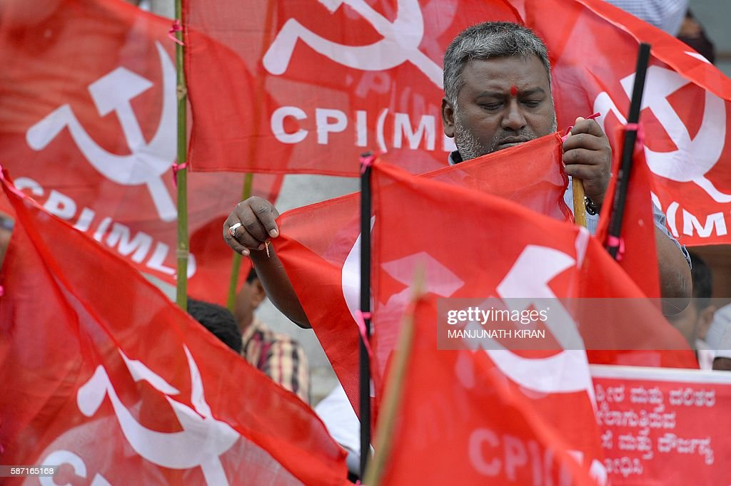 An activist belonging to the Communist Party of India prepares party flags during a protest held by several organisations against the violence in...