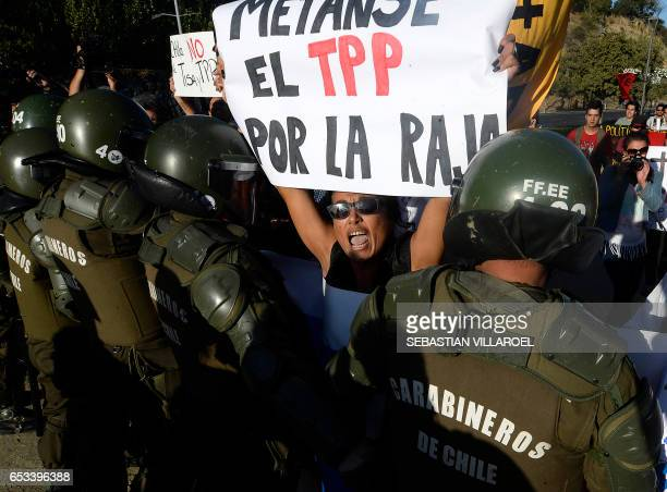 TOPSHOT An activist chants slogans as she confronts carabiniere police during a protest against TTP treaties and the Pacific Alliance Ministers'...