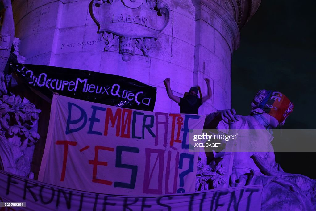 An activist climbs onto the monument at the center of the Place de la Republique to unfold banners during the Nuit Debout, or 'Up All Night' movement on April 28, 2016 in Paris. The 'Nuit Debout' demonstrations began on March 31 in opposition to the government's proposed labour reforms. Banners read 'We occupy better than this' and 'Where are you Democracy.
