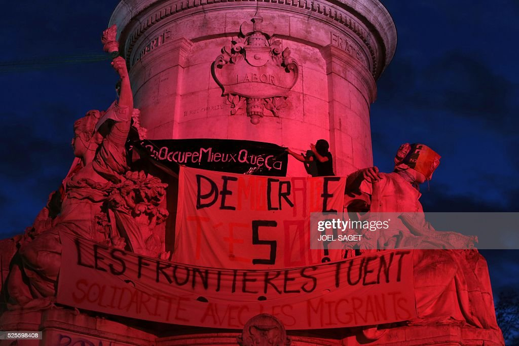 An activist climbs onto the monument at the center of the Place de la Republique, to unfold a banner reading 'We occupy better than this' during the Nuit Debout, or 'Up All Night' movement on April 28, 2016 in Paris. The 'Nuit Debout' demonstrations began on March 31 in opposition to the government's proposed labour reforms. Other banners read 'Where are you Democracy ?', 'Borders are killing' and 'Solidarity with the migrants'.