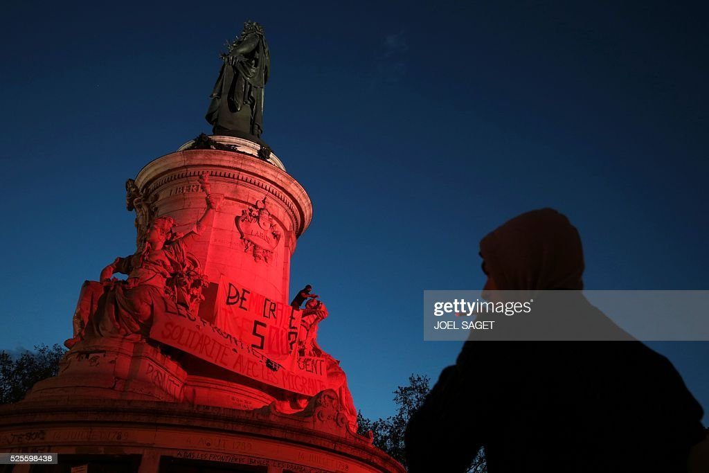 An activist climbs onto the monument at the center of the Place de la Republique to unfold banners during the Nuit Debout, or 'Up All Night' movement on April 28, 2016 in Paris. The 'Nuit Debout' demonstrations began on March 31 in opposition to the government's proposed labour reforms. Banners read 'Where are you Democracy ?', 'Borders are killing' and 'Solidarity with the migrants'.