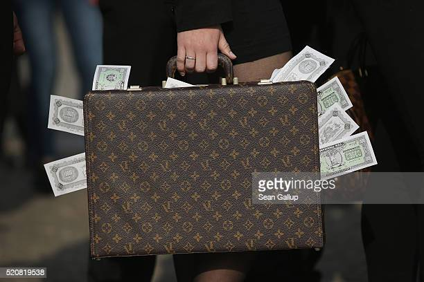 An activist clutching a suitcase stuffed with fake money demands greater trasparency in new legislation following the ongoing Panama Papers affair on...