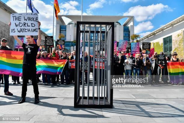 An activist displays a placard before stripping and entering a mock cage in front of the Chancellery in Berlin on April 30 during a demonstration...