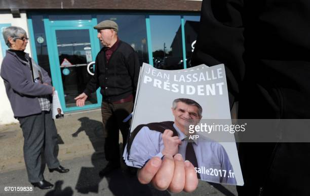 An activist distributes leaflets of French presidential candidate Jean Lassalle few days ahead of the vote's first round on April 18 2017 in Le...