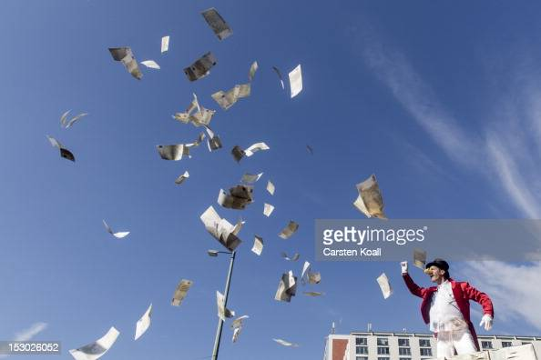 An activist dressed as Scrooge McDuck throws counterfeit money from a golden mountain onto protesters during a demonstration against the increasing...