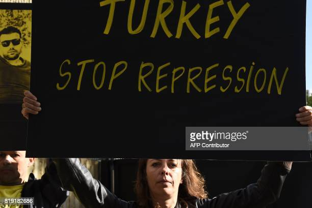 TOPSHOT An activist from human rights NGO Amnesty International holds a sign during a protest outside the Turkish Embassy in Paris on July 20 2017 to...
