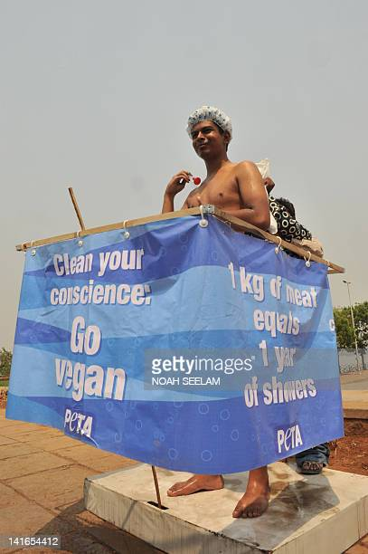 An activist from People for the Ethical Treatment of Animals mimics taking a shower on a roadside in Hyderabad on March 21 to highlight the high...