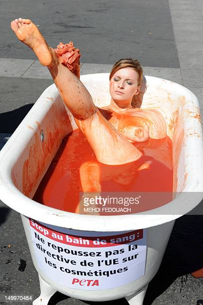 An activist from the association 'People for the Ethical Treatment of Animals' bathes in a bathtub fed up with tomato sauce 'to symbolise a...