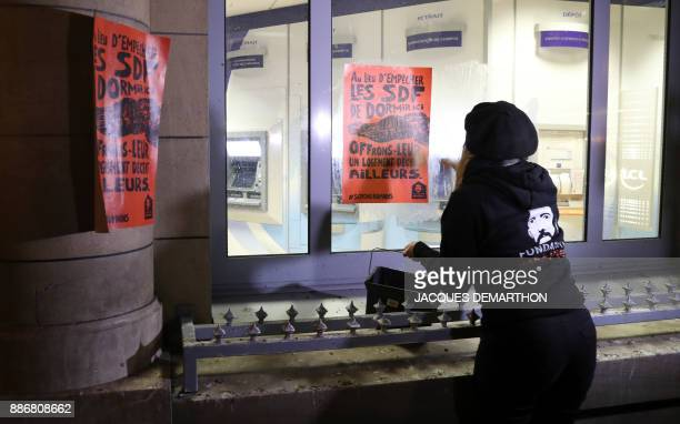 An activist from the Fondation Abbe Pierre foundation sticks leaflets and posters on a bank in Paris on December 6 to highlight the use of...