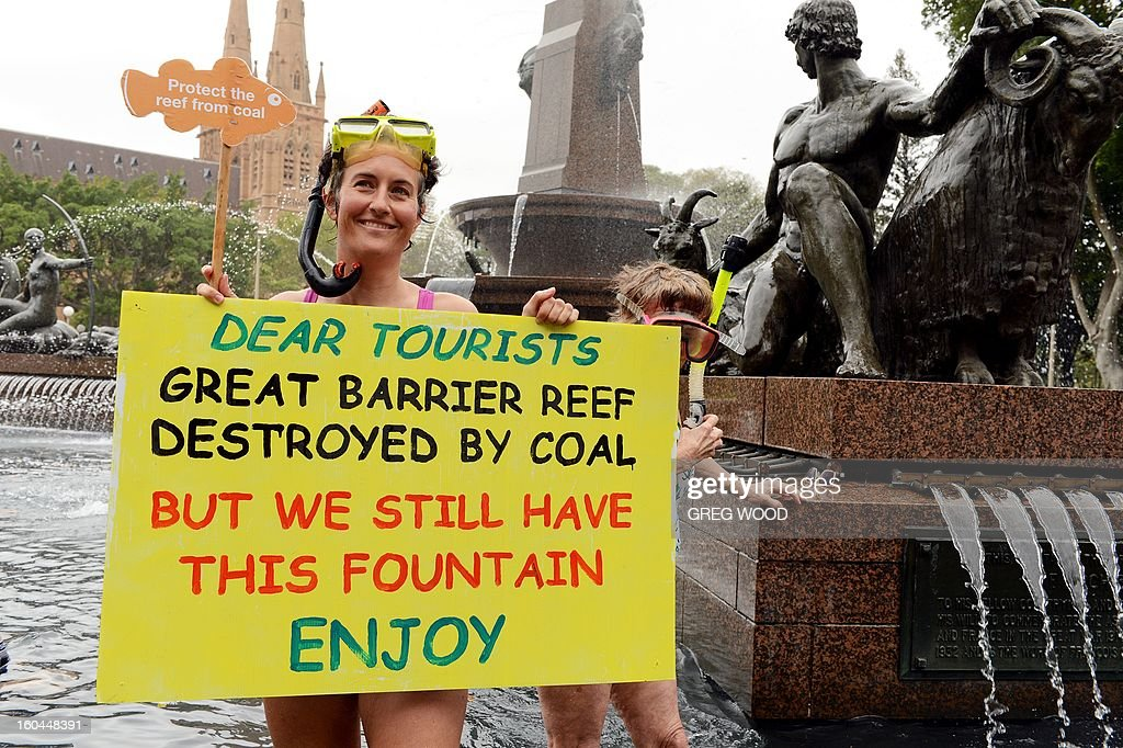 An activist from the 'Protectors of the Reef' collective displays a placard alongside the Archibald Fountain in central Sydney during a protest in support of Australia's Great Barrier Reef on February 1, 2013. Australia insisted on February 1, that protecting the Great Barrier Reef was a top priority, but conservationists WWF said not enough had been done to prevent UNESCO deeming it a world heritage site 'in danger'. AFP PHOTO / Greg WOOD