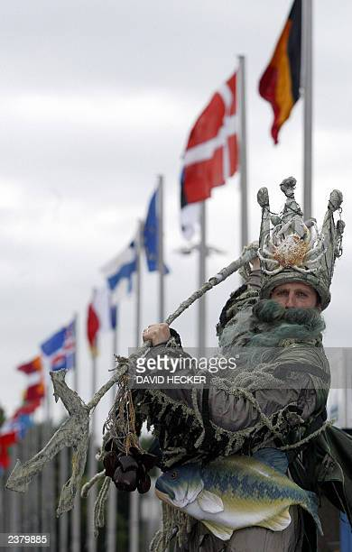 An activist from the World Wide Fund for Nature dressed as Poseidon the ancient Greek god of the sea waves his trident in front of the flags of...
