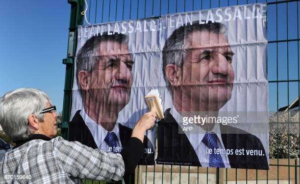 An activist glues campaign posters of French presidential candidate Jean Lassalle few days ahead of the vote's first round on April 18 2017 in Le...