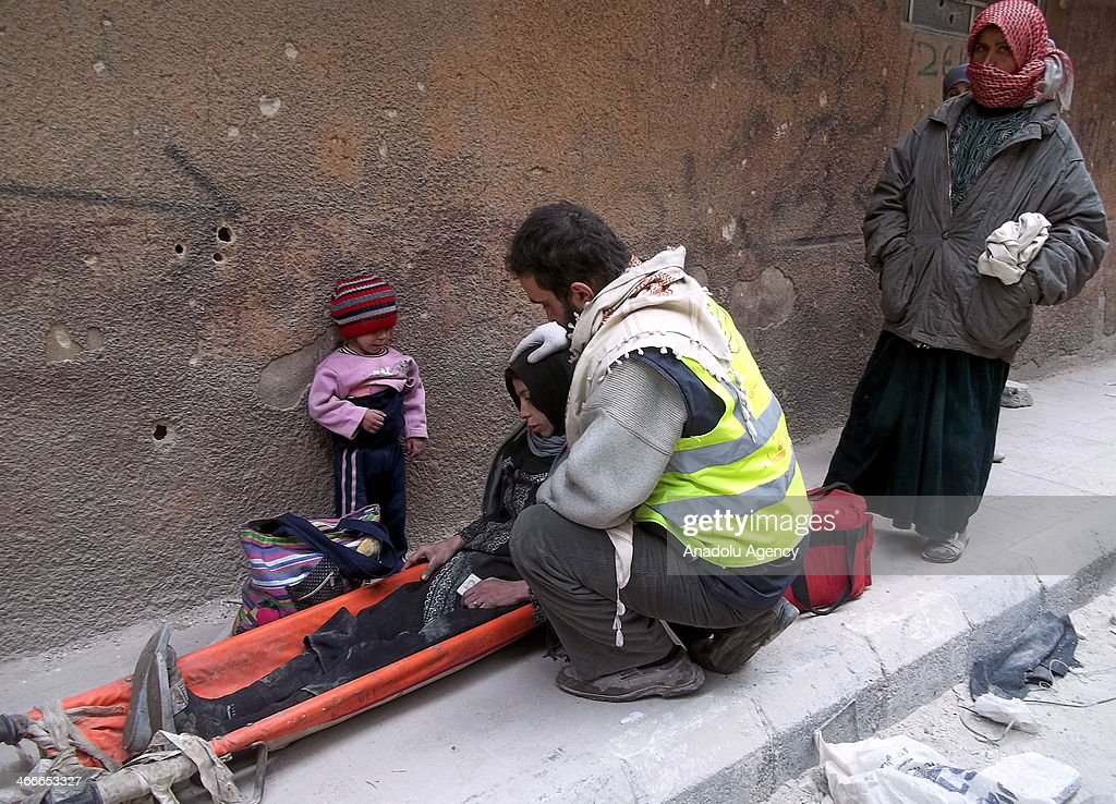 An activist helps a refugee woman at the Yarmouk Refugee Camp, in southern Damascus, Syria, on February 2, 2014.