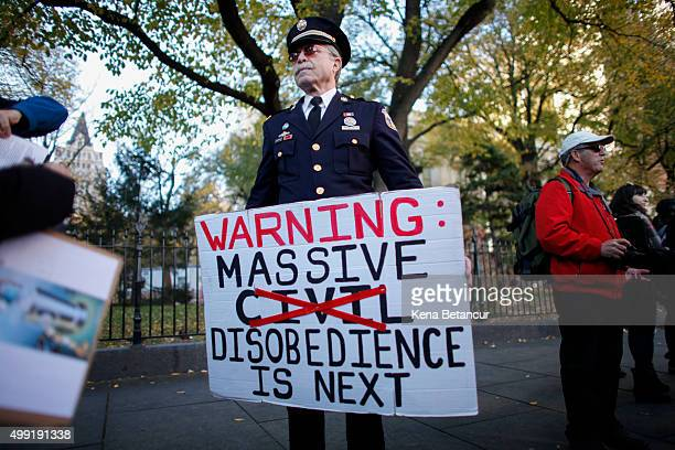 An activist holds a banner as he takes part in a global climate march outside the City Hall on November 29 2015 in New York City The protest is part...