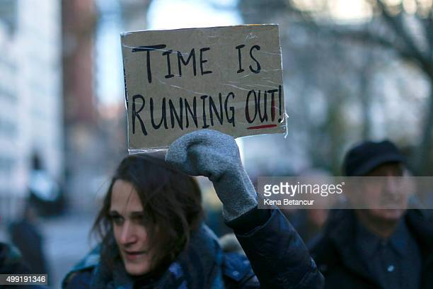 An activist holds a banner as she takes part in a global climate march outside the City Hall on November 29 2015 in New York City The protest is part...