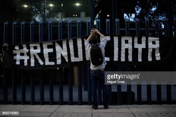 An activist holds a banner during a demonstration against alleged government spying on journalists and human rights defenders outside the attorney...