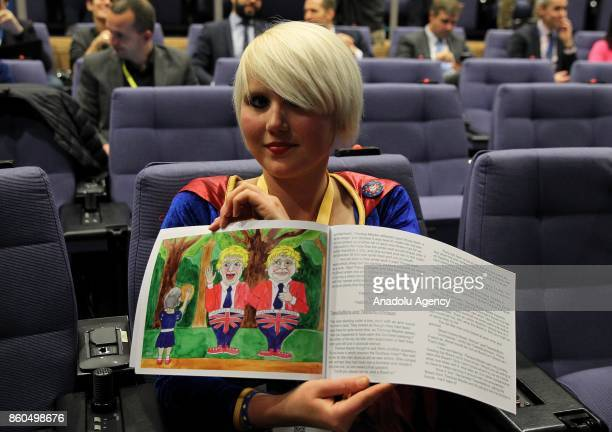 An activist holds a booklet to stage a protest during the joint press conference held by United Kingdom's Secretary of State for Exiting the European...