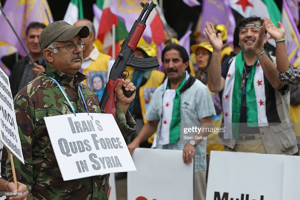 An activist holds a fake assualt rifle while wearing a sign refering to involvement of Iranian troops in Syria at a demonstration of mostly expatriate Iranian opposition activists protesting against Iranian support of the government of Syrian President Bashar Assad on August 16, 2012 in Berlin, Germany. Meanwhile the Organization of Islamic Cooperation suspended Syria's membership during its current summit in Mecca.