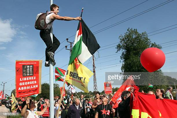 An activist holds a Palestinian flag while climbing a pole as people take part in a protest calling for the liberation of Lebanese activist Georges...