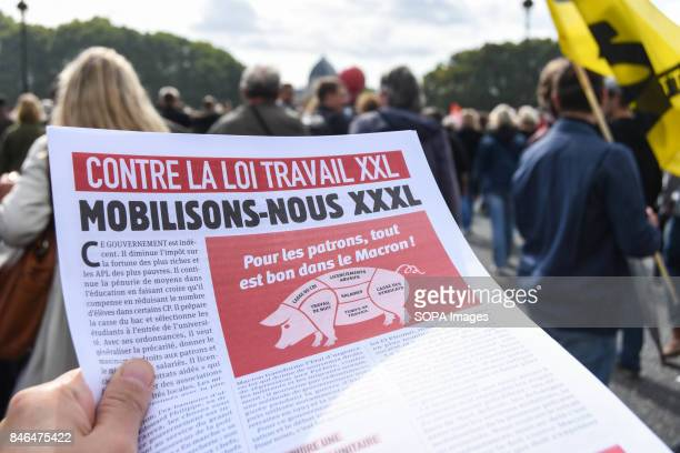 An activist holds a paper writing on it Against the labour law reform' take part in a protest during the nationwide strike called by various French...