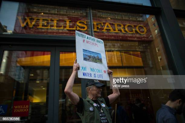 An activist holds a placard at the entrance of Wells Fargo bank as activists begin the overnight camp out in front of the bank on April 5 2017 in...