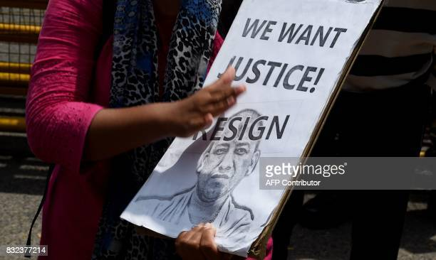 An activist holds a placard calling on Uttar Pradesh Chief Minister Yogi Adityanath to resign during a protest rally outside the Uttar Pradesh state...